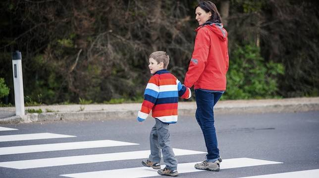 Mother and son crossing the street on the crosswalk