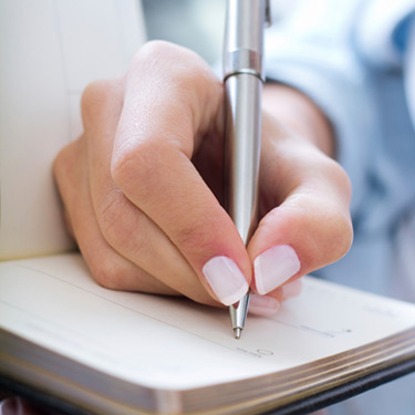 young-woman-taking-notes-at-home_web